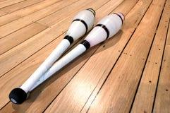 Jetez les clubs en l'air de jonglerie sur une étape en bois de plancher Image libre de droits