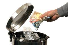 Jetez un paquet de billets de banque dans les déchets photographie stock