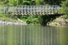 Jetez un pont sur à l'intérieur de la forêt qui est reflétée dans le wate de lac Photos stock