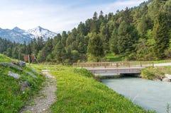 Jetez un pont sur traverser une rivière glaciaire devant les Alpes français Photographie stock libre de droits