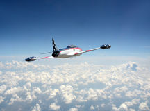 Jetfighter in American colors. Jetfighter in US flag colors above the clouds Royalty Free Stock Image