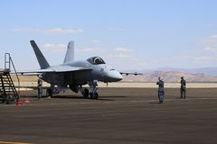 Jetfighter on Nevada tarmac. Military jet fighter on a tarmac in Reno, Nevada with mountain backdrop and sky with clouds royalty free stock photography