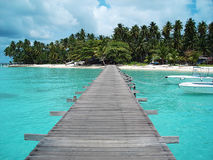 Jeti to paradise. Jeti leading to beautiful tropical island with luxury boat parked nearby Stock Image