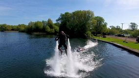 Jetlev flyer, athlete, sportsman flying and chasing camera before turning off stock video footage
