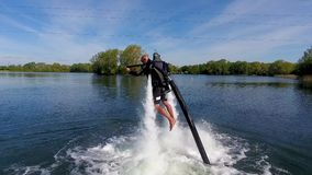 Jetlev flyer, athlete, sportsman prepares and then takes off with water jet levitation pack stock video footage