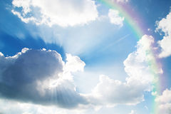 A jetliner aeroplane flying over white clouds towards a rainbow. In blue sky royalty free stock photos