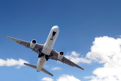Jetliner in blue sky. Bottom view of a jetliner flying in the sky stock photography