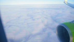 Jetliner flies above white dense clouds under blue sky