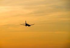 Jetliner flying against red sunset sky Stock Photos