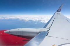 Jetmotorn och påskyndar en Boeing 737-800 som flyger på 30.000 fot ovanför vitmoln Arkivfoto