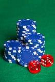 Jetons de poker bleus et deux cubes sur la table verte Image stock