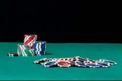 Jetons de poker colorés sur le fond vert images stock
