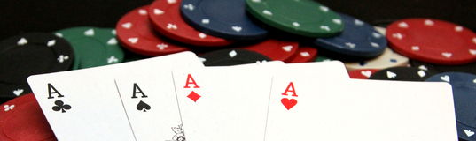 Jetons de poker et quatre as sur l'ordinateur portable Images stock