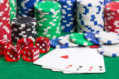 Jetons de poker, matrices et quatre as sur la table verte Image stock