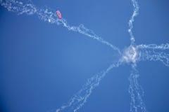 Jets asteroides del humo y un skydiver minúsculo en una mucha altitud en un cielo azul Imágenes de archivo libres de regalías