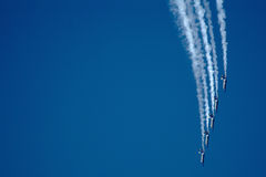 Jets and Contrails. Precision flying jets leave arcing contrails on a blue sky Royalty Free Stock Images