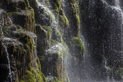 The jets and drops of water against the black rocks . Jets and water drop waterfall in the mountains on a background of black rock , covered with green grass Royalty Free Stock Images