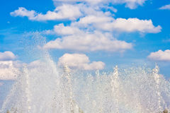 Jets of a fountain. On a background of the blue sky with clouds Stock Photography