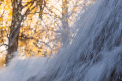 Jets waterfall autumn background. The jets of a waterfall on the background of autumn trees. Can be used as wallpaper Stock Photos