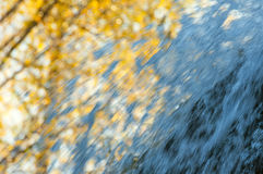 Jets waterfall autumn background. The jets of a waterfall on the background of autumn trees. Can be used as wallpaper Royalty Free Stock Photo