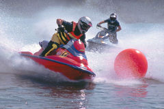 Jetski. Two jet skis running out a red buoy and splashing Stock Images
