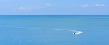 Jetski, das auf einem blauen Wasser und einem blauen Himmel läuft stockfotografie