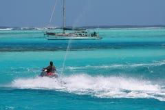 Jetski passing a sailboat Stock Image