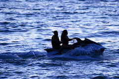 Jetski People. Is a couple riding a jetski silhouetted against the deep blue sea at evening time stock photography