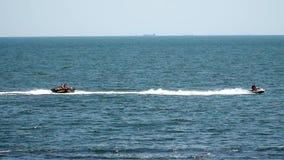 Jetski on the sea pulls inflatable mattress stock video footage