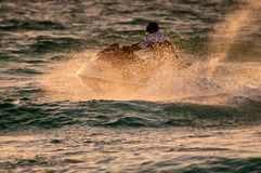 Jetski silhouette. And water droplets in sunset royalty free stock photography
