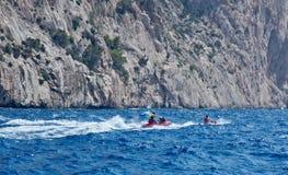 Jetskiers  speeding in seaspray Royalty Free Stock Images