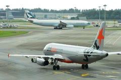 Jetstar亚洲空客320为离开做准备当国泰空中客车330出租汽车过去 免版税库存照片