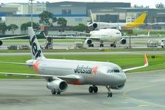 Jetstar亚洲空客320乘出租车低成本的载体装门在樟宜机场 免版税库存照片