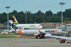 Jetstar Ásia Airbus A320 e Air Zimbabwe Boeing 767 estacionaram no aeroporto de Changi Fotos de Stock