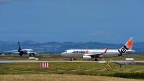 Jetstar и аэробус A320s Air New Zealand соперника ездя на такси на международном аэропорте Окленда Стоковое Изображение RF
