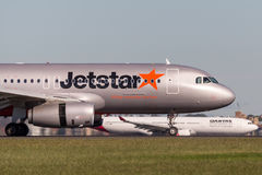 Jetstar Airways Airbus A320 airliner landing at Sydney Airport with a Qantas aircraft in the background. Stock Photography