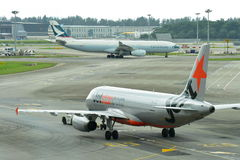 Jetstar Asia Airbus 320 preparing for departure as Cathay Pacific Airbus 330 taxi past Royalty Free Stock Photo