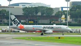 Jetstar Asien Airbus 320, der an Changi-Flughafen mit einem Taxi fährt Lizenzfreie Stockfotografie