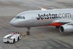 Jetstar Asien Airbus 320, der für Abfahrt zurückgeschoben wird Lizenzfreies Stockfoto