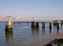 Jetties on the Tejo river shore in Almada, Portugal.  Portugal. Jetties on the Tejo river shore in Almada, Portugal. In the distance the skyline of Lisbon Royalty Free Stock Photography