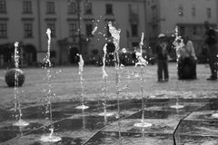 The jetting of the fountain in the city square. Krakow, Poland, Europe Royalty Free Stock Photo