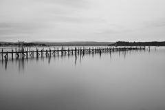 Jetty. A pier or jetty for boats, made of many wooden struts, on a still water, with an island visible in the background Royalty Free Stock Photos