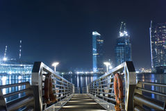 The Jetty. Looking down the jetty towards parts of the skyline at Marina Bay, Singapore Stock Image