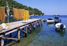 The Jetty. Fishing nets drying on a jetty with fishing boats. Corfu, greece stock photos