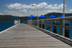 Jetty. A wooden jetty at a low angle featuring shade umbrellas in Australia Royalty Free Stock Images