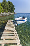 Jetty at Agni, Corfu. Jetty with boat attached looking out to blue sky, sea and tree covered rocks Stock Image