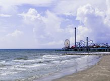 Historic Pleasure Pier on the gulf coast in Galveston, Texas. A jetty alongside historic Pleasure Pier provides a landing for fishing, and fun, food and stock photos