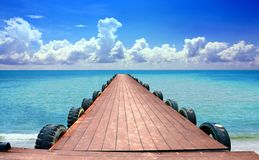 Jetty at the beach with cloudy blue sky Royalty Free Stock Photography
