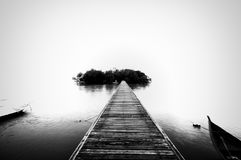 Jetty, boat and island in black and white Royalty Free Stock Photos