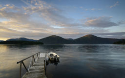 Jetty and boat at sunrise in the fjord Stock Photography